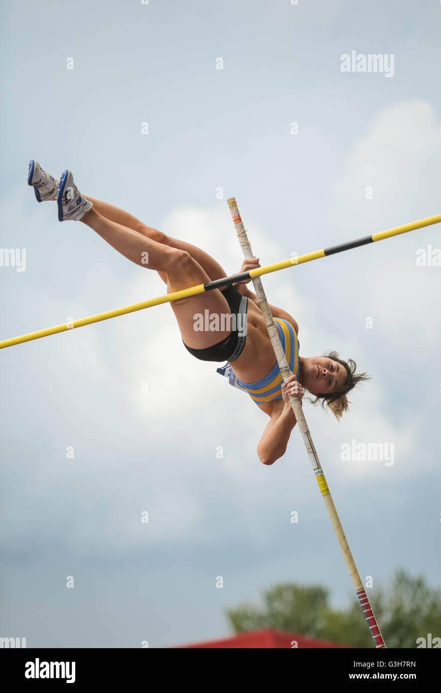 A pole vault athlete photographed in the air - Stock Image