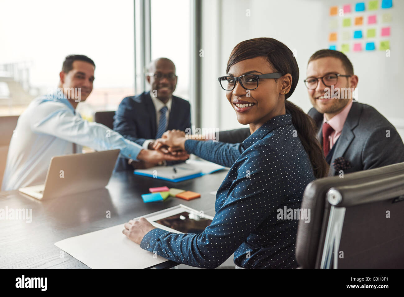 Successful African American team leader turning to smile at the camera as her multiracial team of executives links - Stock Image