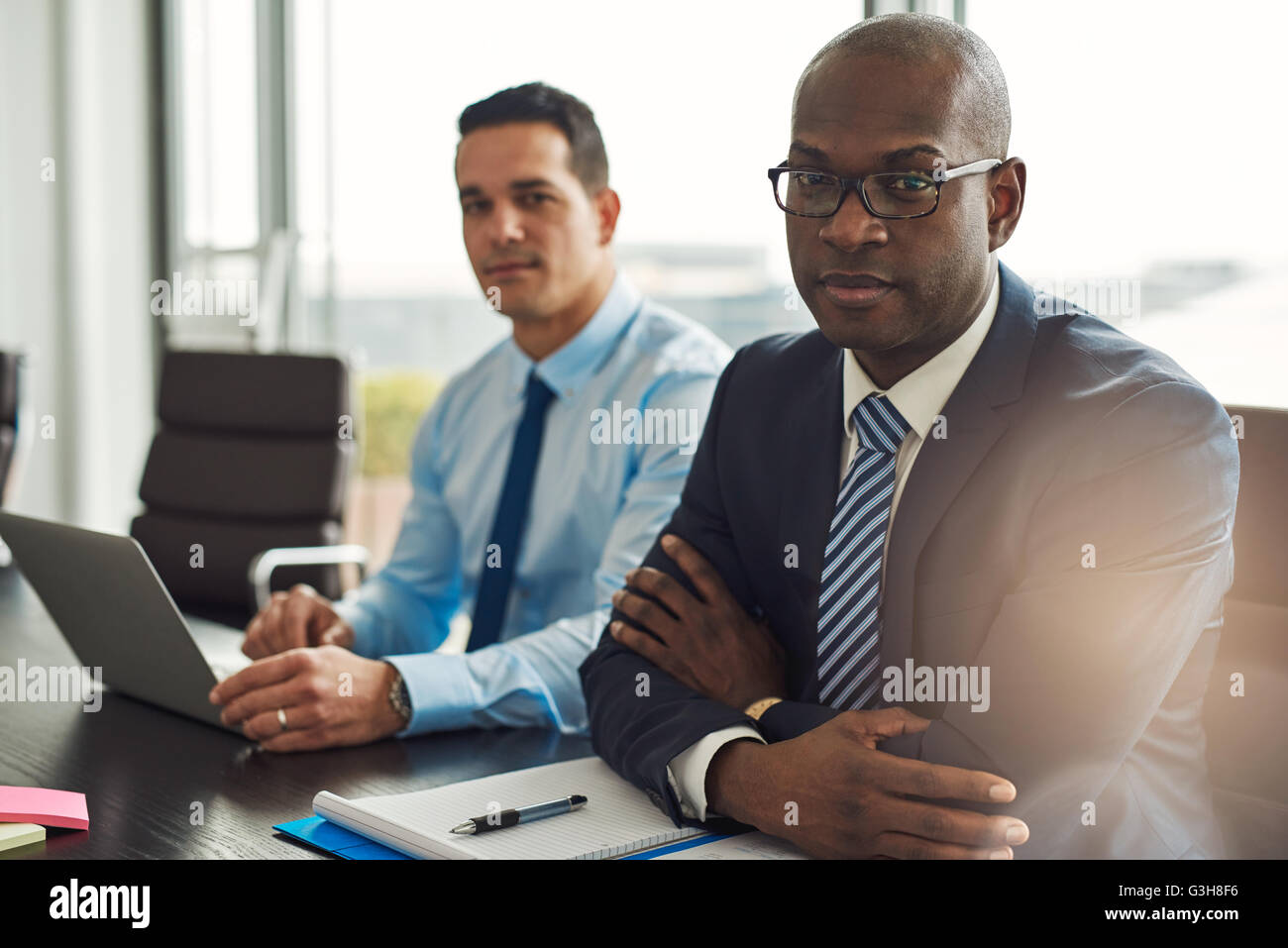 Successful multiracial business partners in a meeting together with a young Hispanic man using a laptop and African - Stock Image