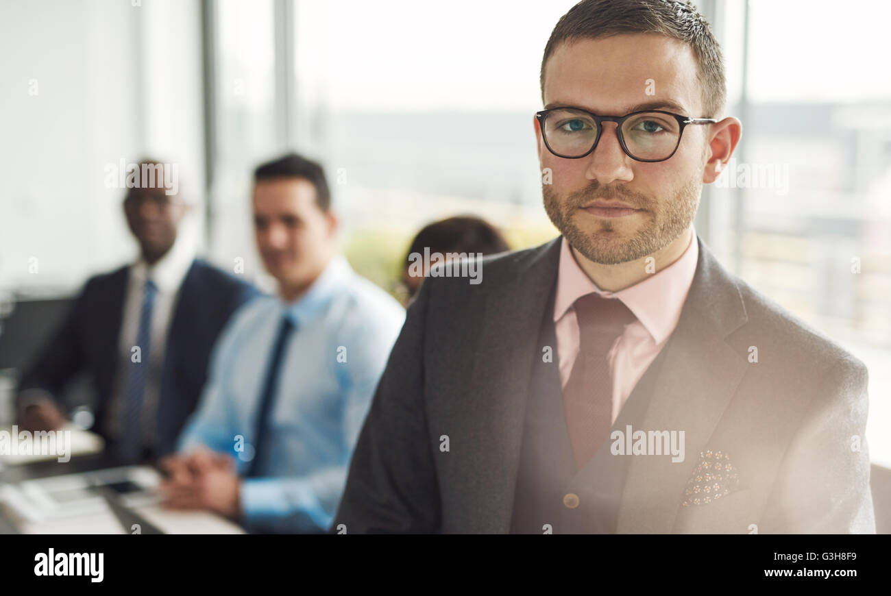 Serious young businessman in a meeting with multiracial colleagues standing looking intently at the camera with - Stock Image
