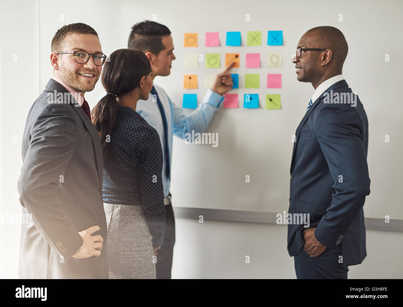Group of businesspeople solving a puzzle on colorful memo notes on a wall with a young male executive at the rear - Stock Image