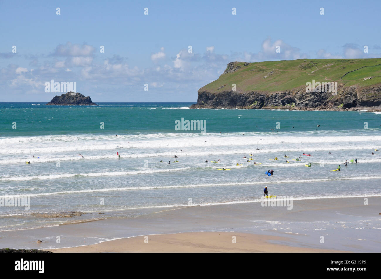 Polzeath beach - incoming tide - white topped rollers - surfers - blue sea and sky - backdrop Pentire Head Cornwall - Stock Image