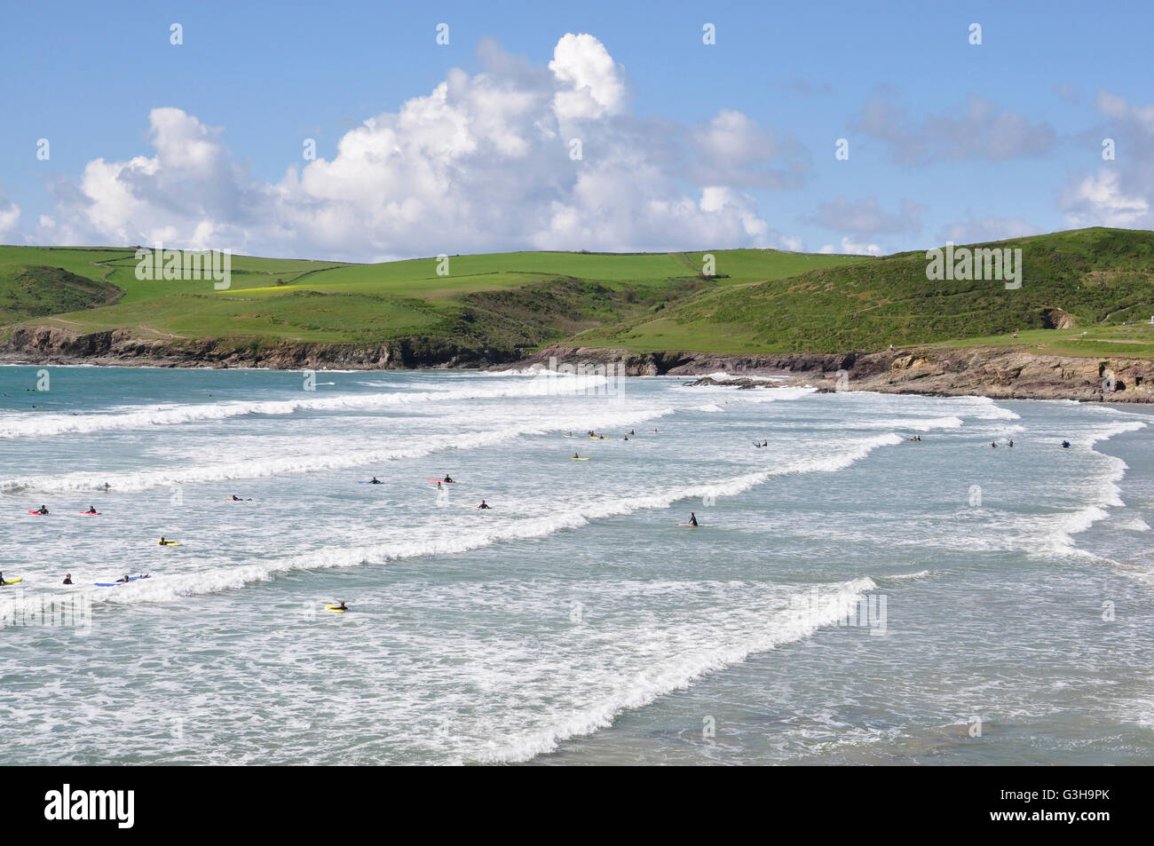 Cornwall - Polzeath beach - white capped rollers - surfers - backdrop Pentire head - blue sea and sky bright summer - Stock Image