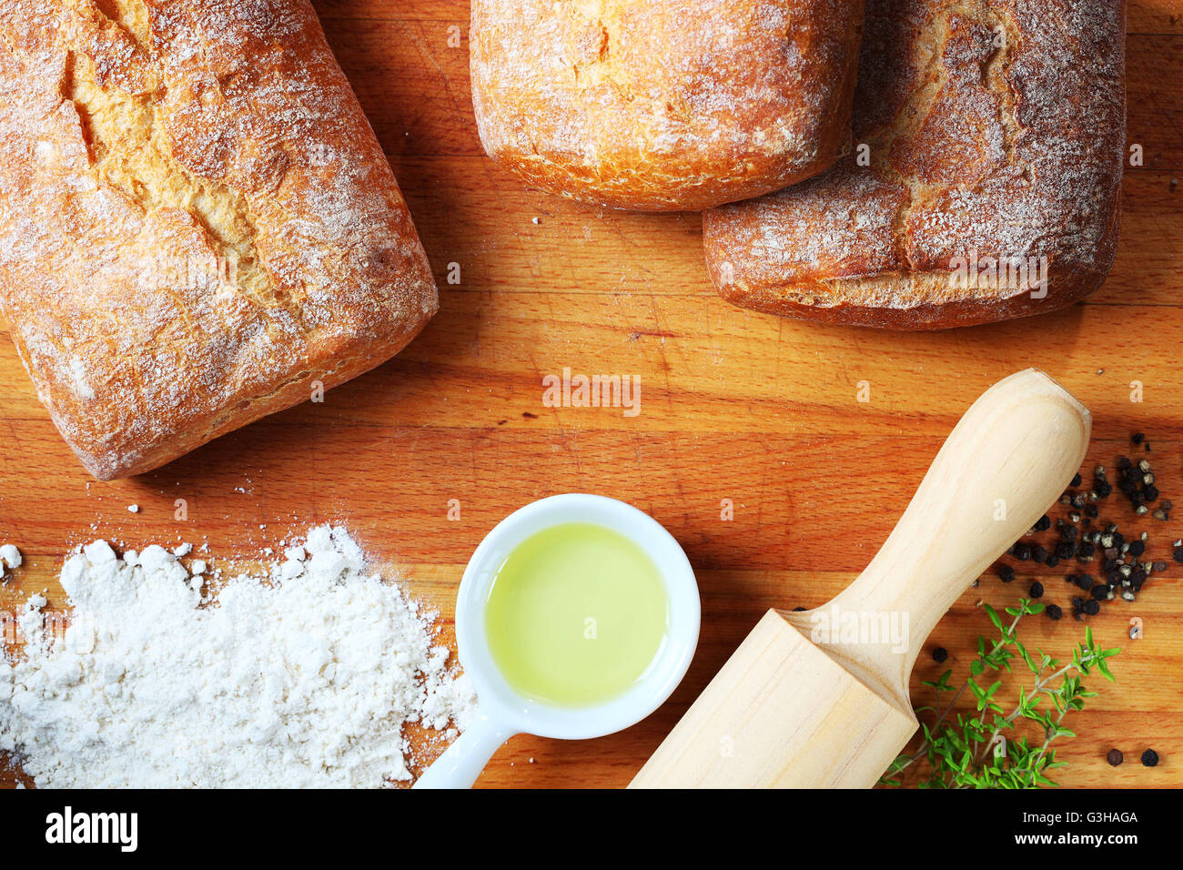 Artisan bread with ingredients on a wooden table. - Stock Image