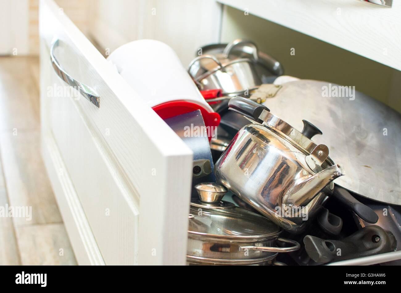 drawer pots pans steel teapot - Stock Image