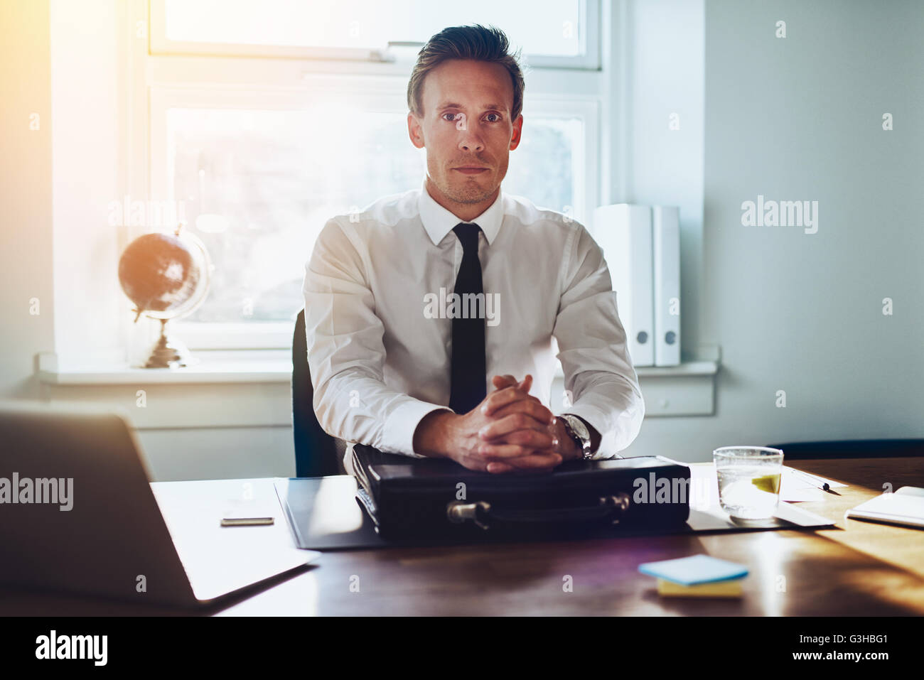 Executive business man at his desk looking with authority at the camera, hands folded on brief case at desk - Stock Image