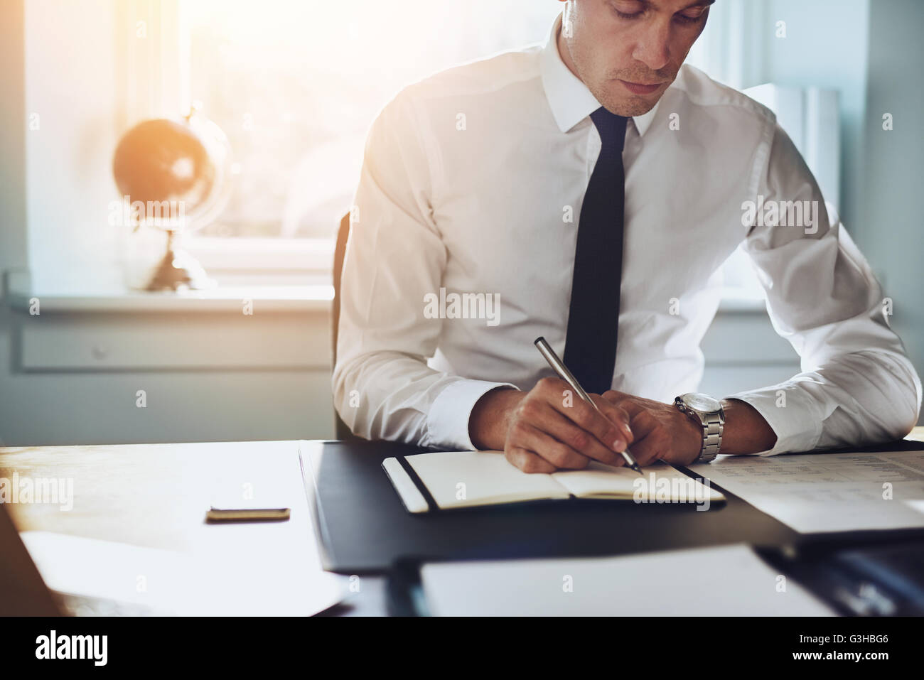 Close up of business man in shirt and tie working in his office writing in a classic note book - Stock Image