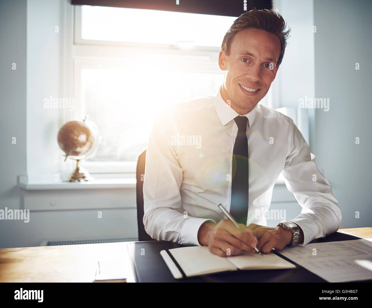 Business man executive writing notes while smiling at the camera, wearing white shirt and tie - Stock Image