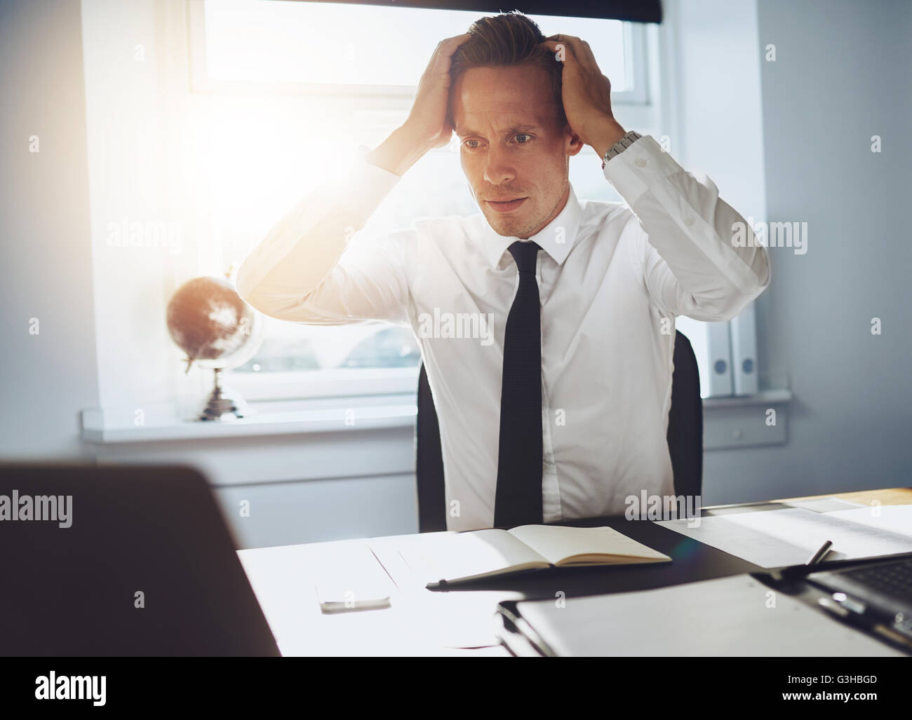 Frustrated business man looking at laptop holding his hands to his head in frustration - Stock Image