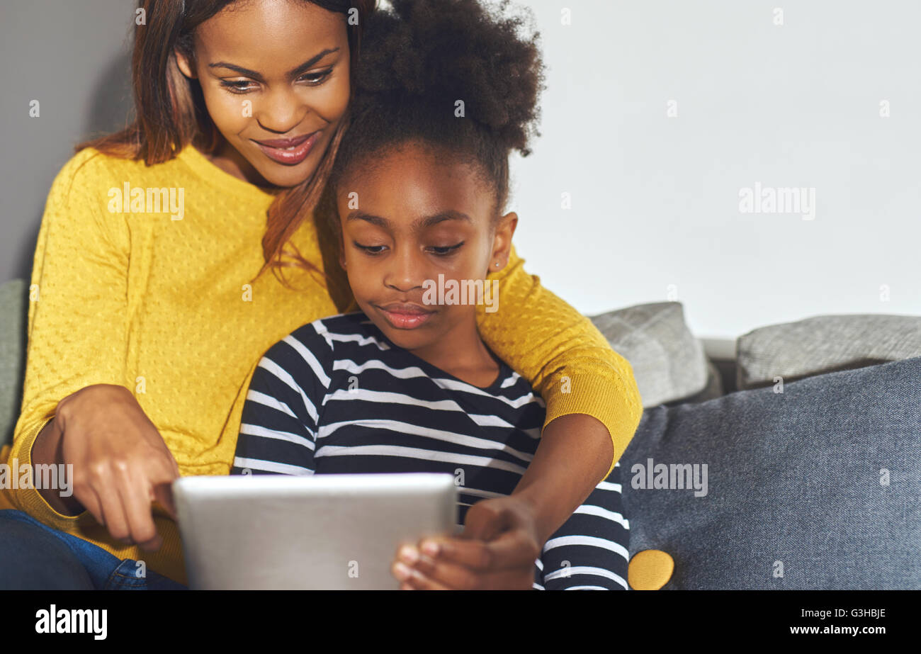 Black mom and daughter learning on tablet sitting at home in sofa Stock Photo
