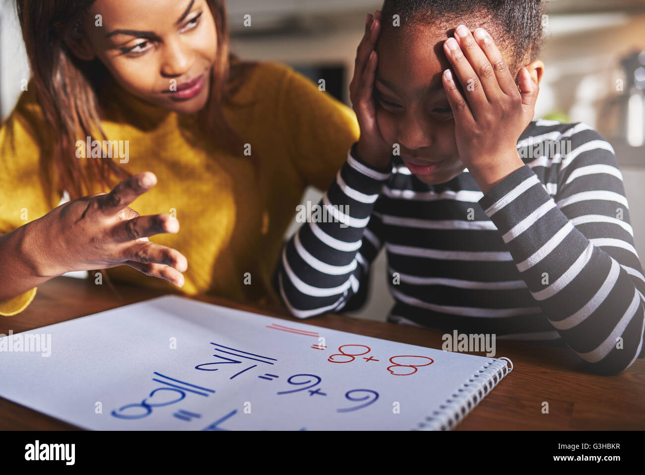 Mother learning child to calculate, child looking frustrated. Black woman and child - Stock Image