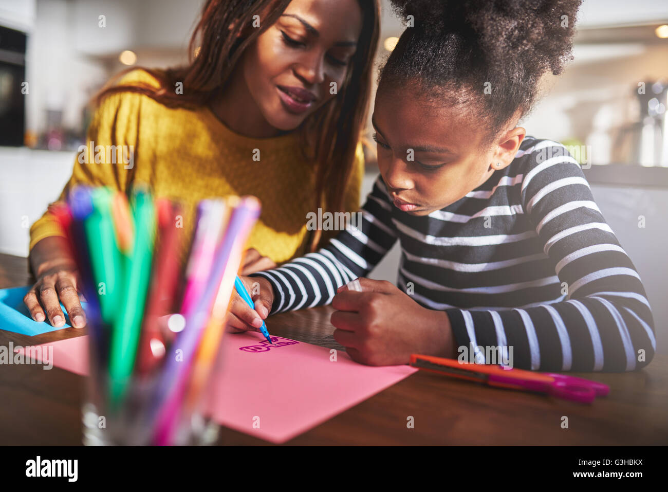 Mom and child drawing in kitchen, black mother and daughter - Stock Image
