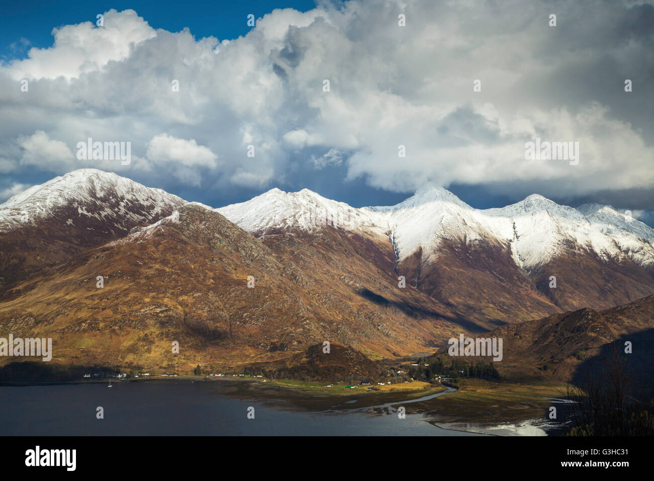 Snow capped summits of the Five Sisters of Kintail tower over Loch Duich, Western Highlands, Scotland - Stock Image