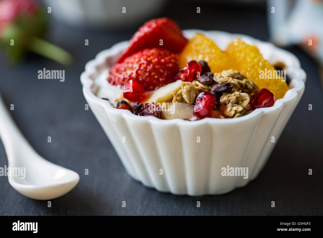 Granola with Orange, Strawberry, Cacao nibs and Pomegranate on yogurt - Stock Image