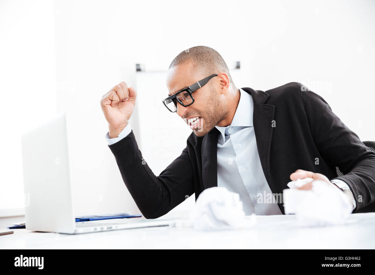 Angry nervous businessman working at office desk overloaded with paperwork - Stock Image