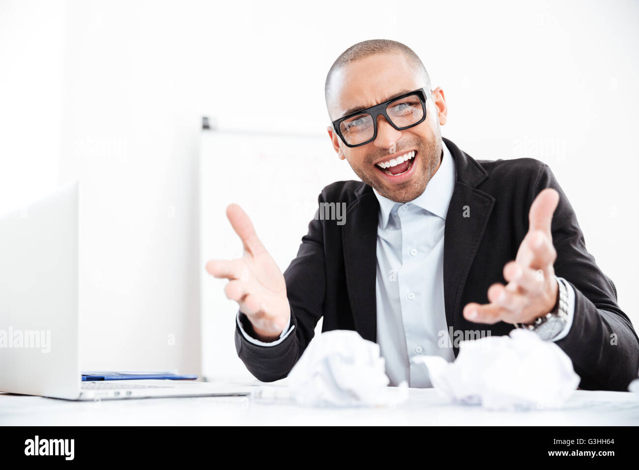 Angry nervous businessman working at office desk overloaded with paperwork and shouting at camera - Stock Image