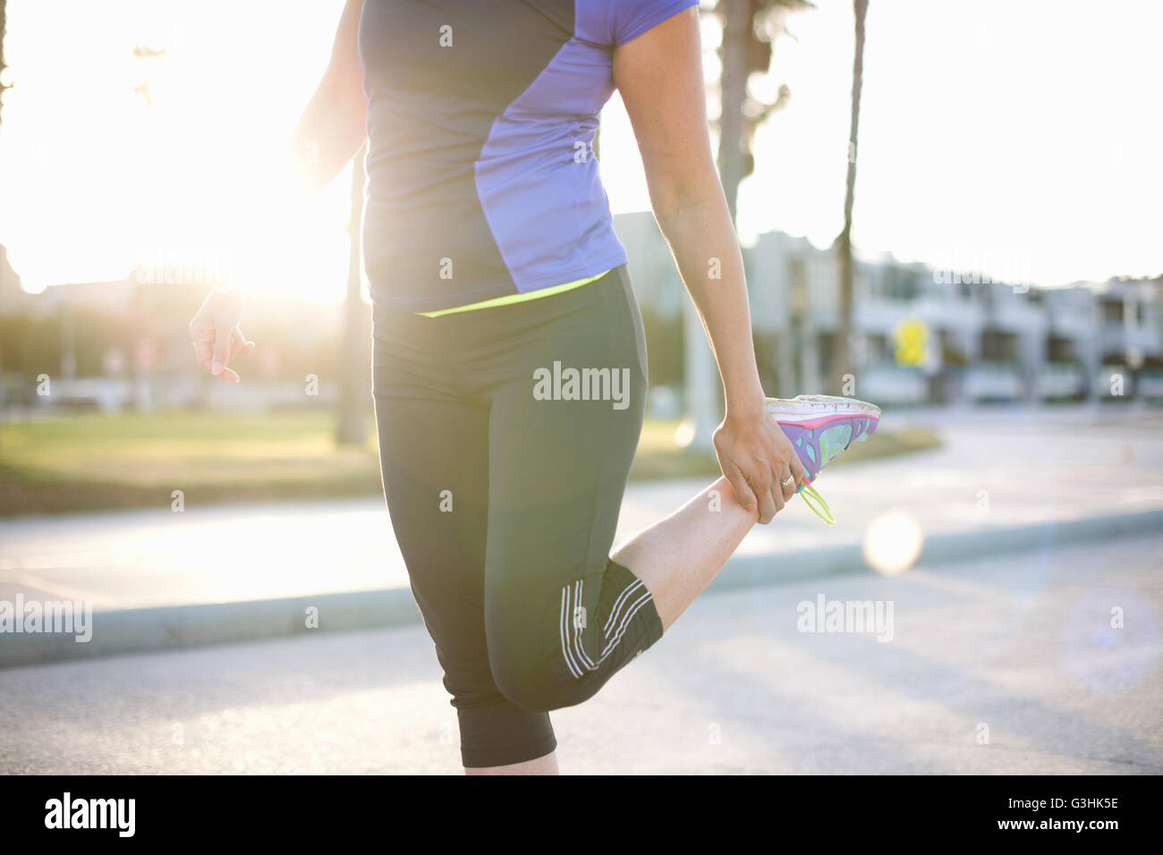 Mid section of woman wearing sports clothes holding ankle stretching leg - Stock Image