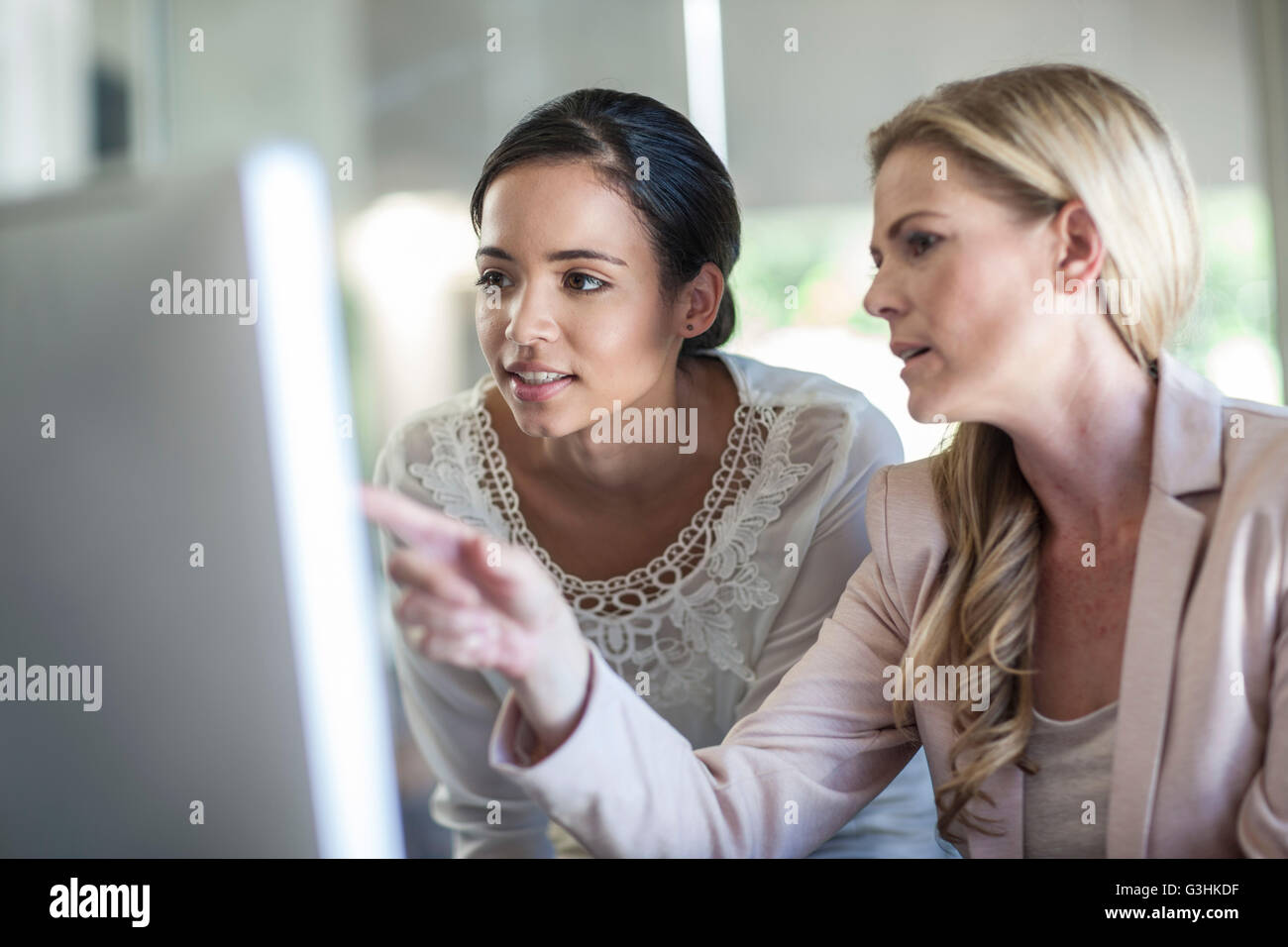 Businesswomen looking at personal computer at office desk - Stock Image
