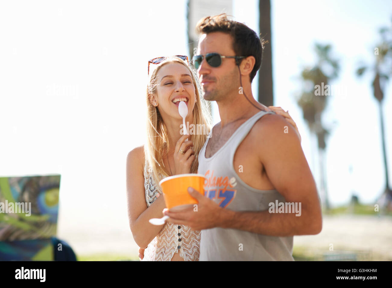 Couple strolling and eating frozen yoghurt at Venice Beach, California, USA - Stock Image