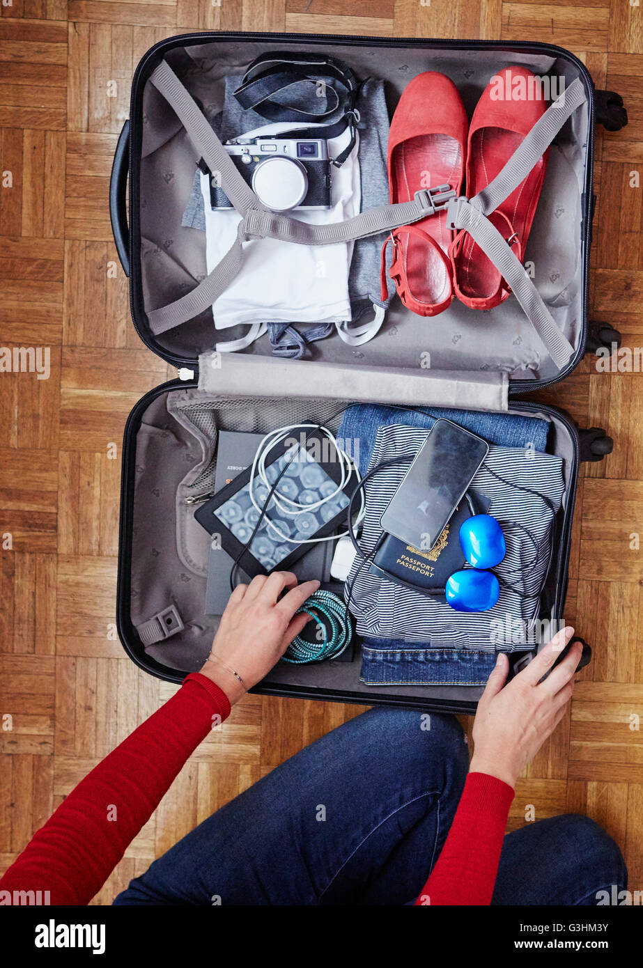 Woman packing suitcase, overhead view Stock Photo