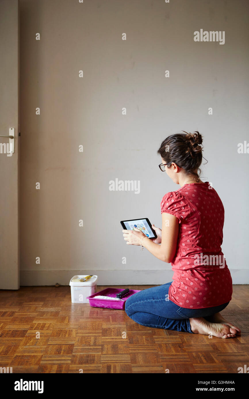 Woman kneeling beside decorating equipment, looking at digital tablet, rear view - Stock Image