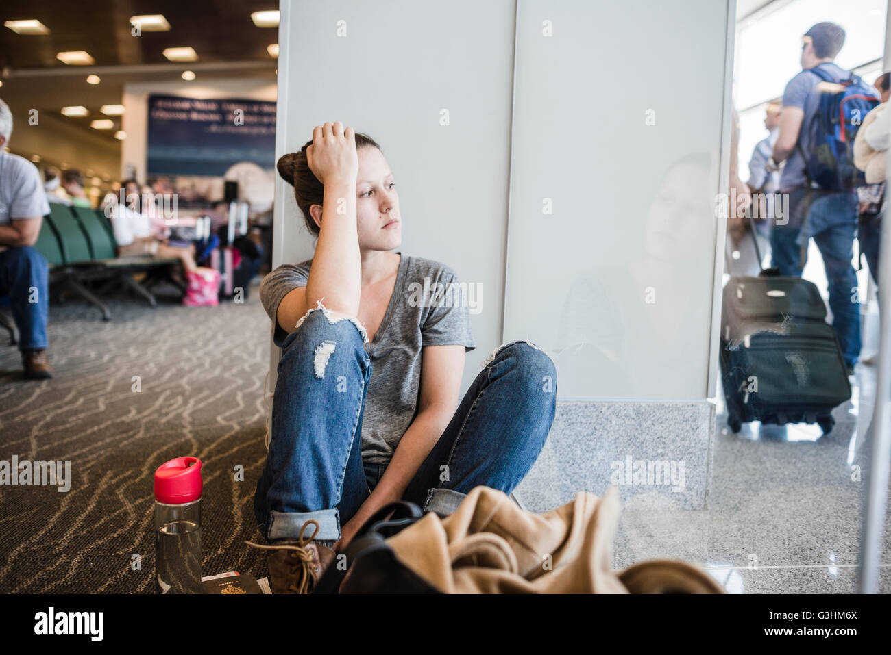 Fed up young woman sitting on airport floor, Liberia, Guanacaste, Costa Rica - Stock Image