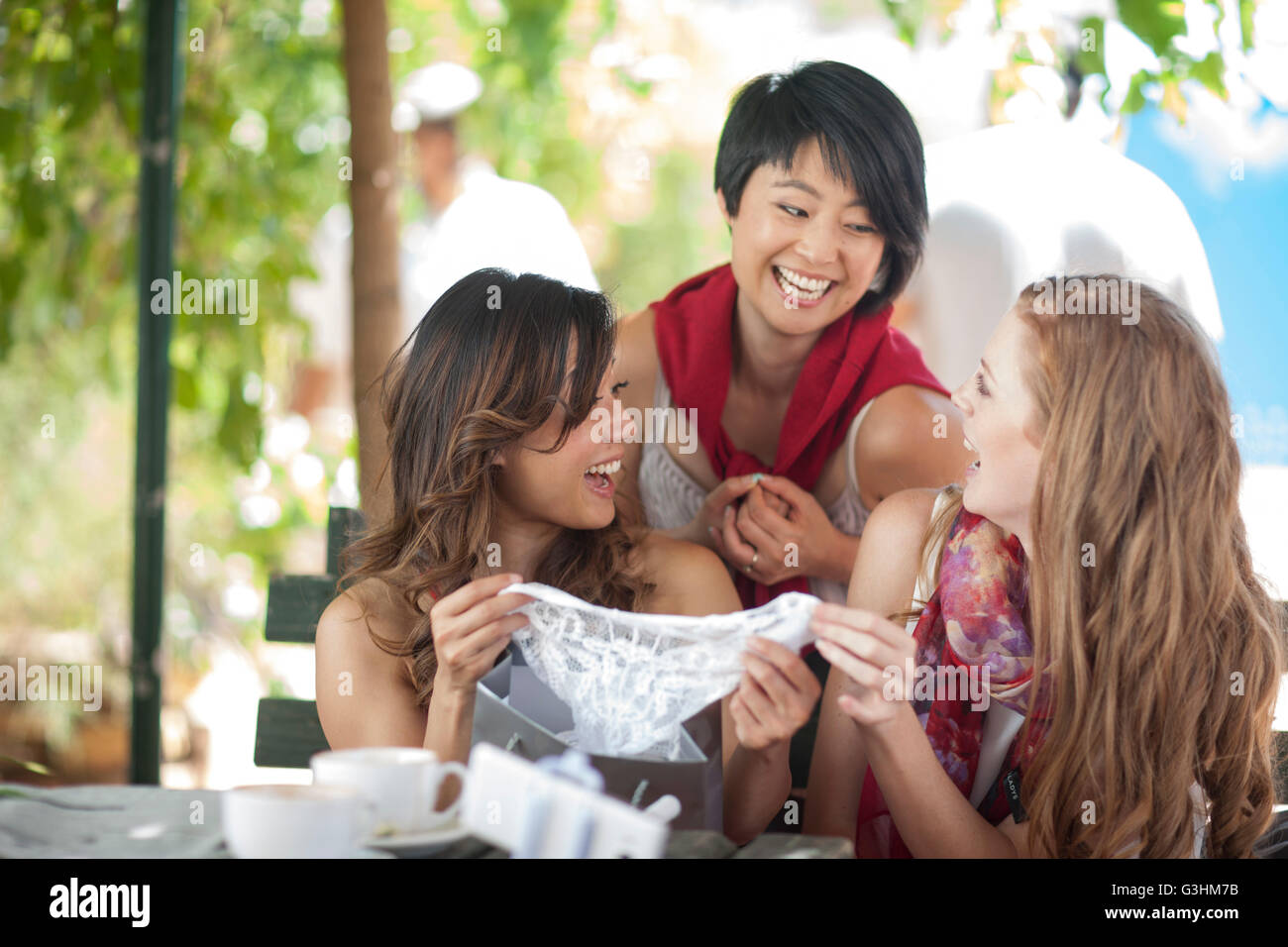 Three female shopping friends laughing at new knickers at sidewalk cafe in city - Stock Image