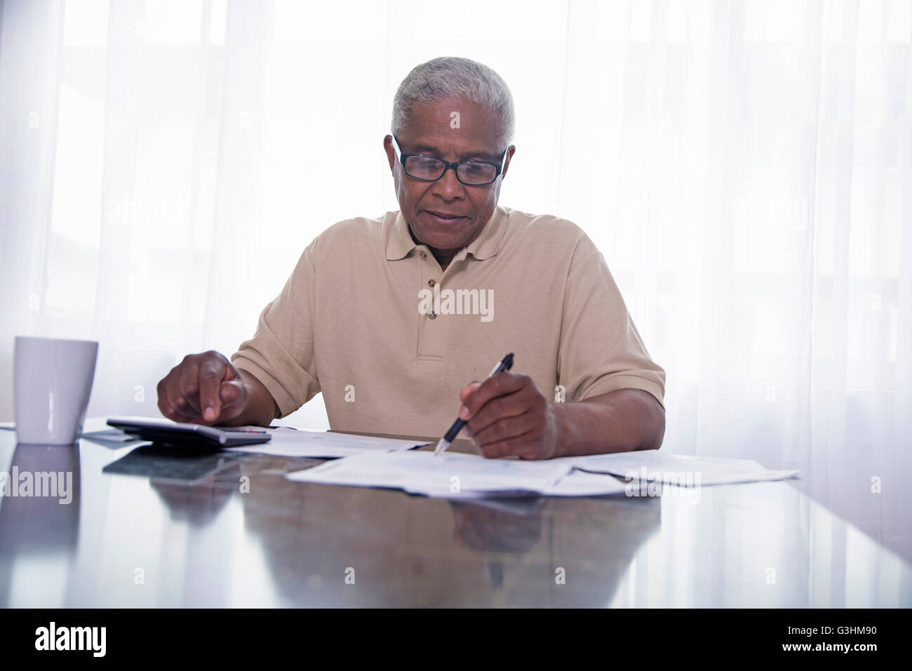 Senior man sitting at table, doing paperwork - Stock Image
