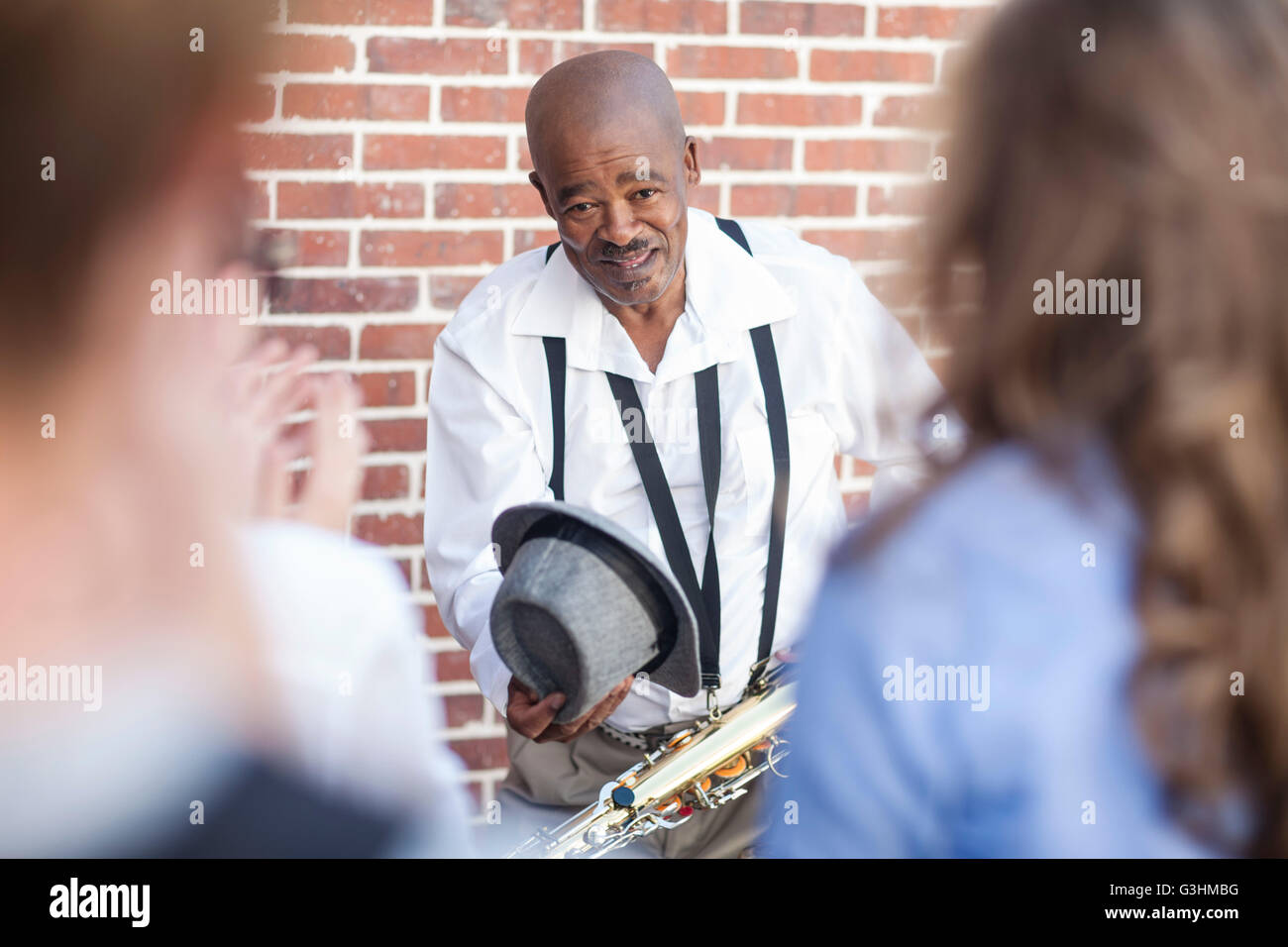 Street musician bowing to crowd - Stock Image