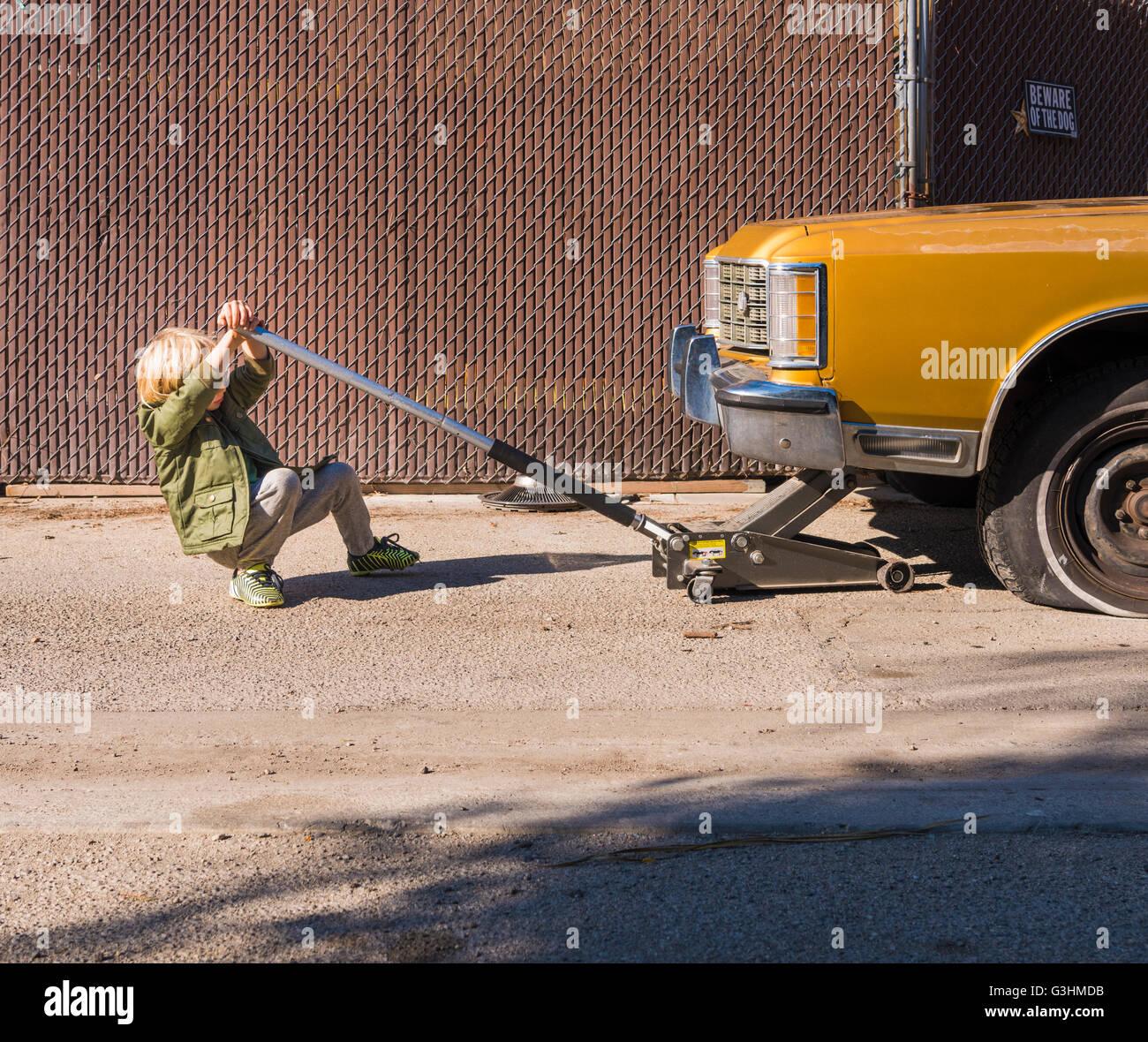 Boy using car jack to raise car - Stock Image