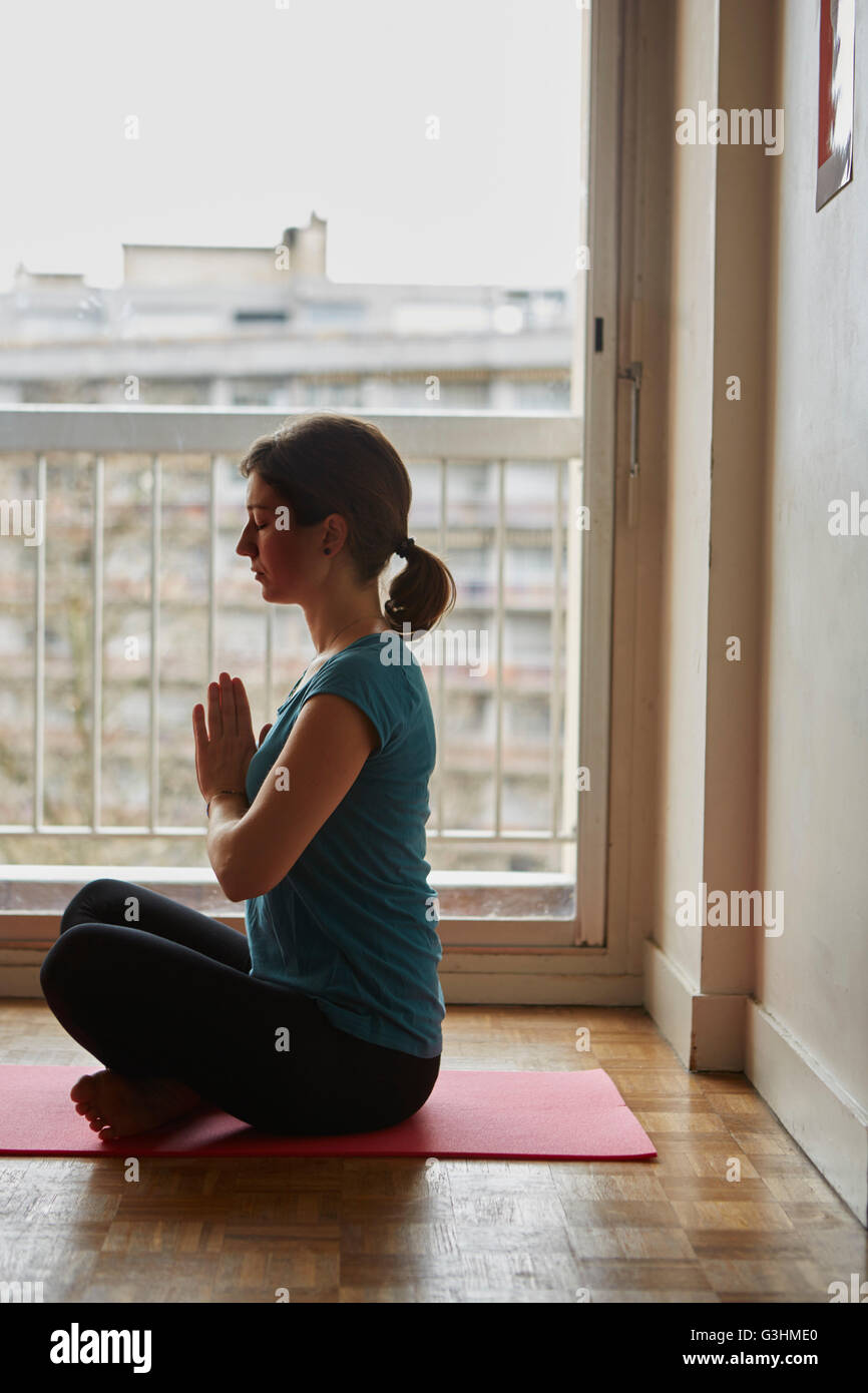 Side view of woman sitting cross legged, hands together meditating - Stock Image