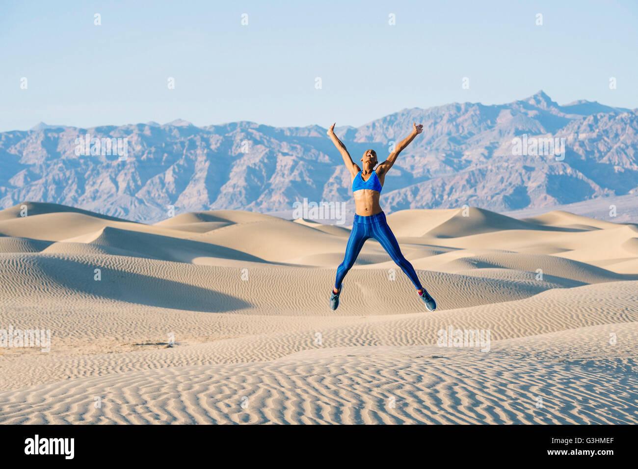 Runner doing star jumps in desert, Death Valley, California, USA - Stock Image