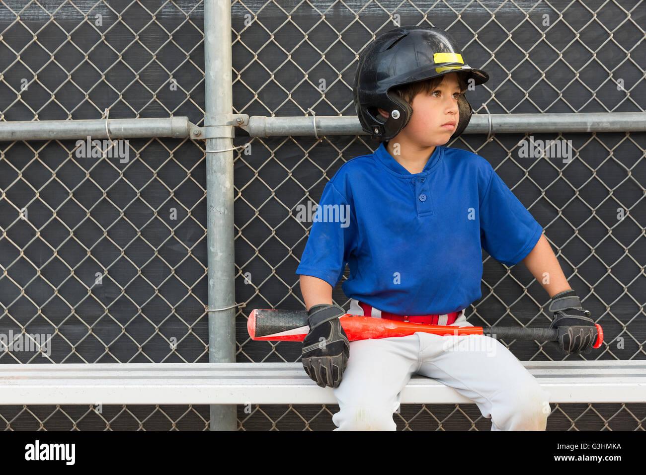 Boy with baseball bat watching from bench at baseball practise - Stock Image