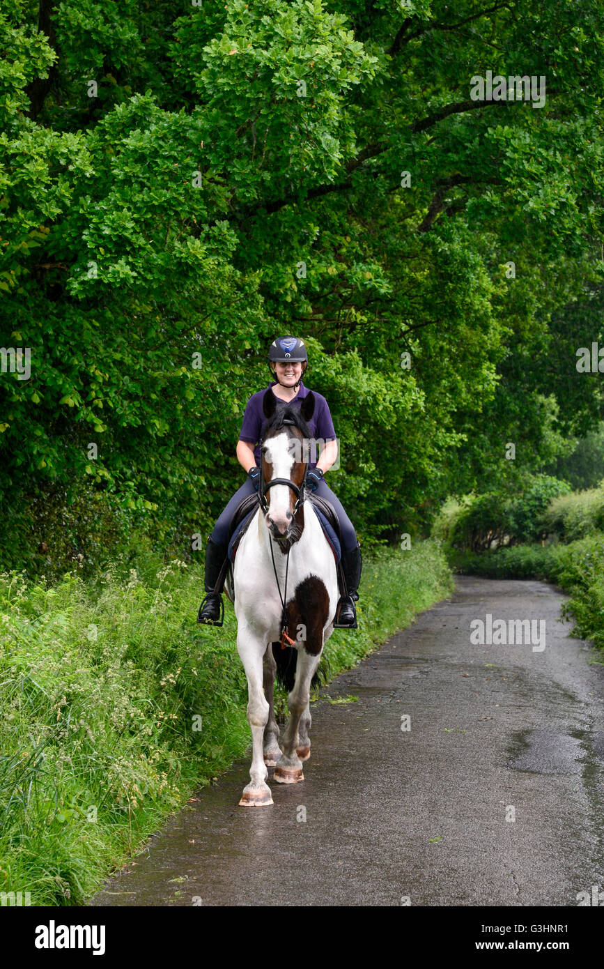 Horse rider on a country lane on a rainy summer day. Smile on the face of the rider despite the wet weather. - Stock Image