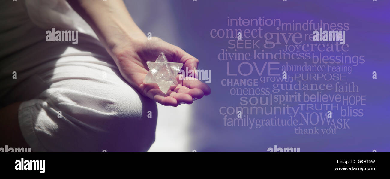 Female sitting in Lotus Position with sunlight streaming in holding a large Merkabah crystal and mindfulness word - Stock Image