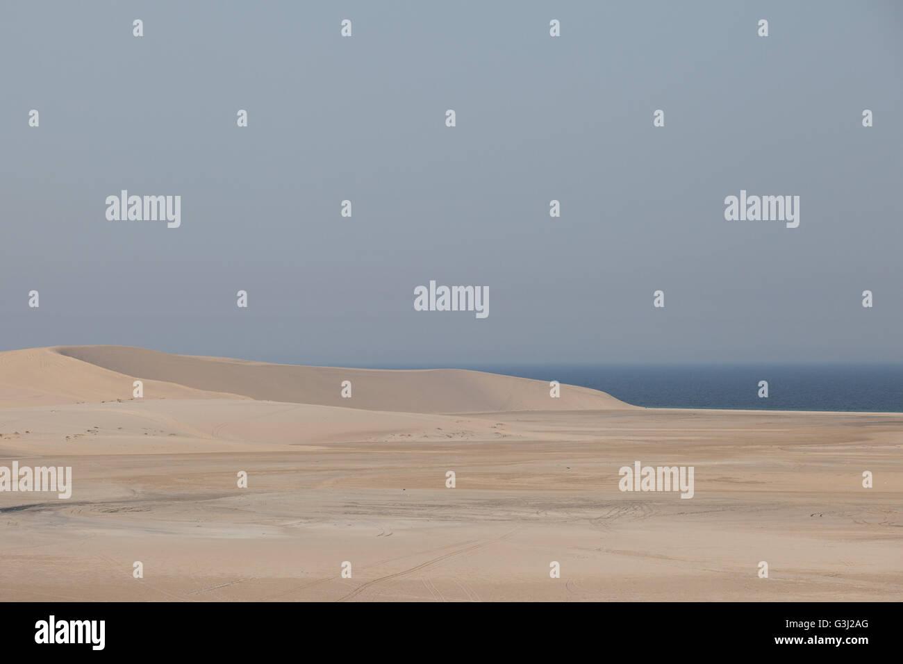 Sand dune, desert in Qatar, next to inland sea. - Stock Image