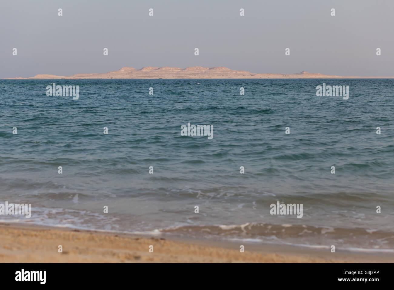 The coast of Saudi Arabia viewed from the Qatar coast across the inland sea. - Stock Image