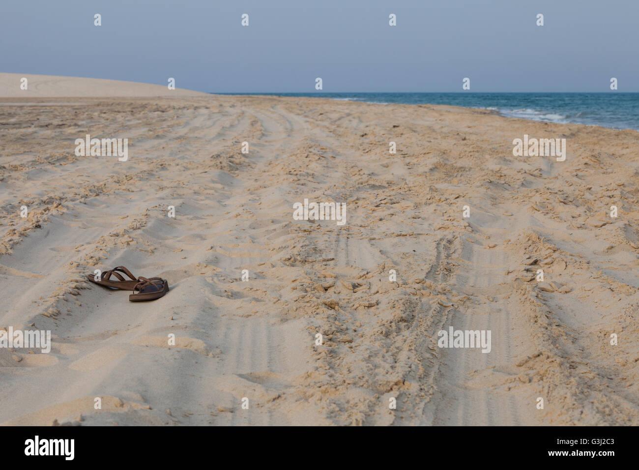 The coast of  Qatar.  Abandoned leather sandals. - Stock Image