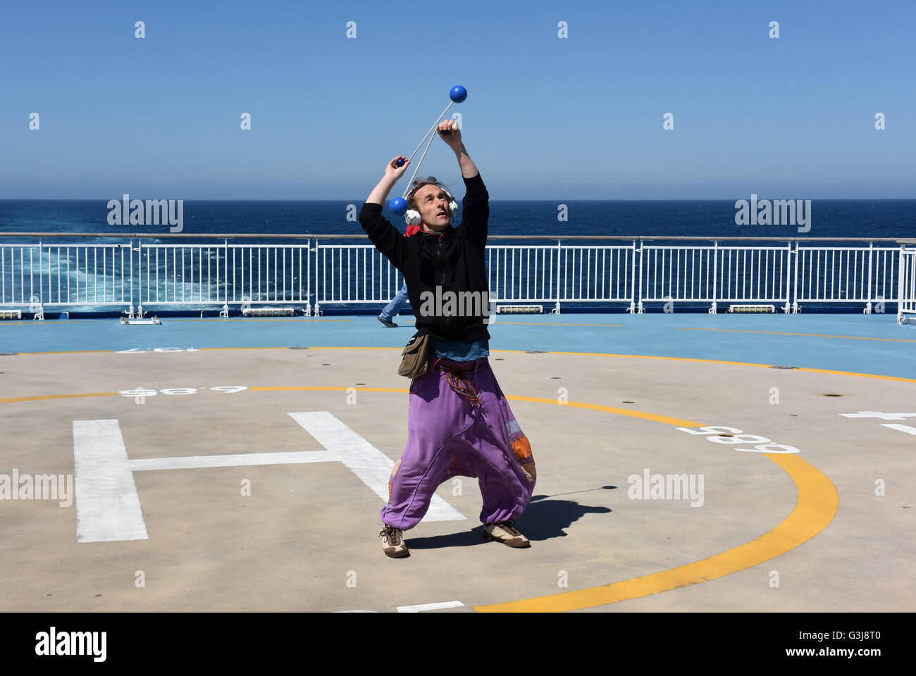 Man juggling on deck of MV Pont-Aven the Brittany Ferries cruiseferry sailing between Portsmouth and Santander. - Stock Image