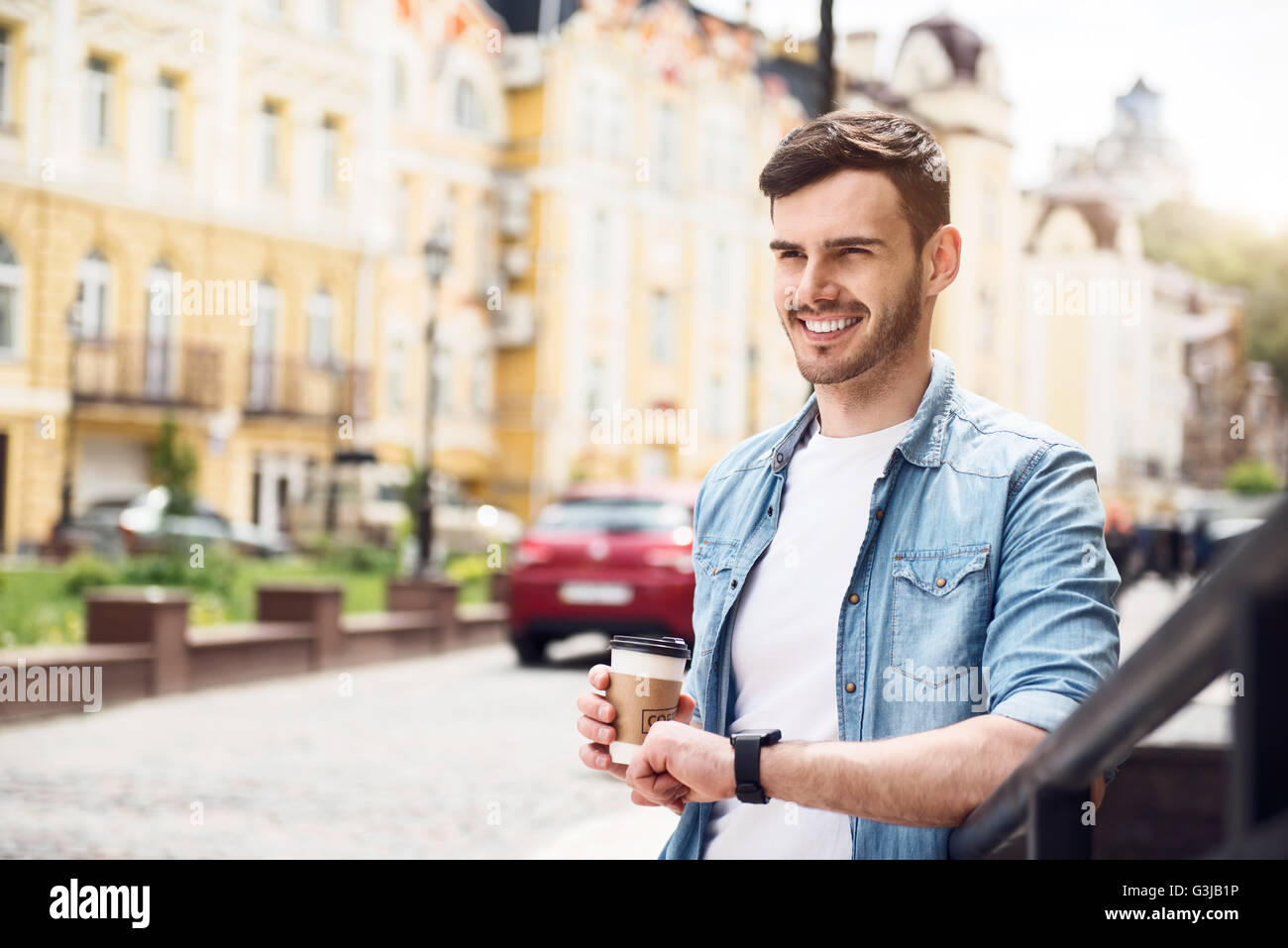 Positive man leaning on the handrail - Stock Image