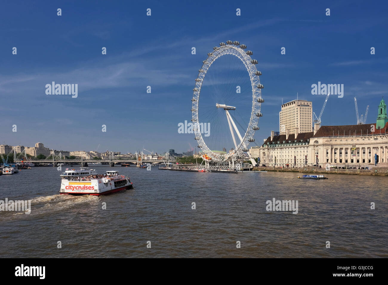 A cityscape from Westminster Bridge which includes the London eye and sightseeing boat on the Thames. - Stock Image