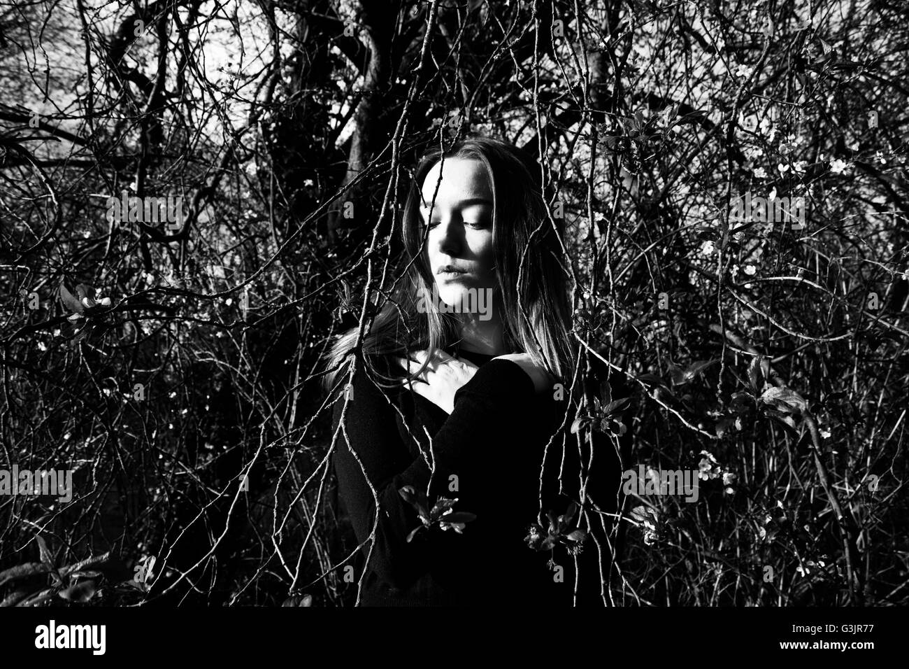 Lost, depressed girl in the woods. Black and white image. - Stock Image