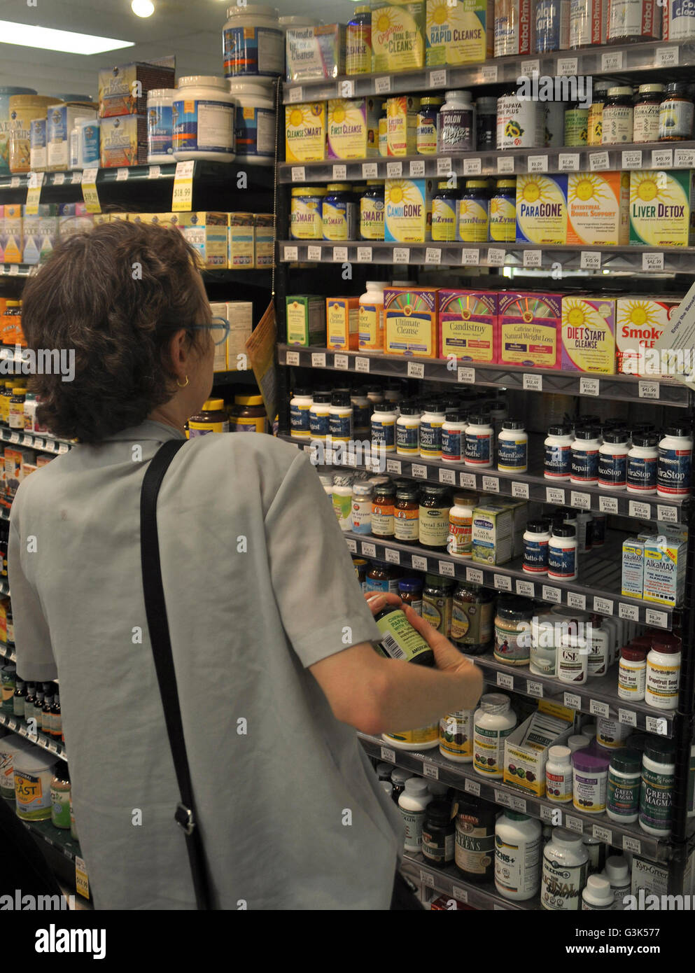Woman looking at the different vitamins in a health food store in College Park, Maryland - Stock Image