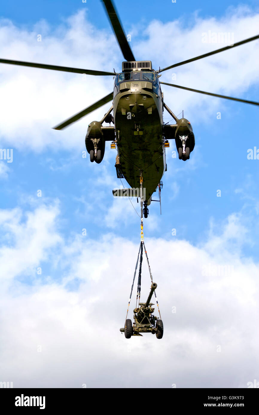 A Royal Navy Westland Sea King HC.4 helicopter with an underslung load of a 105mm light gun at the RNAS Yeovilton - Stock Image