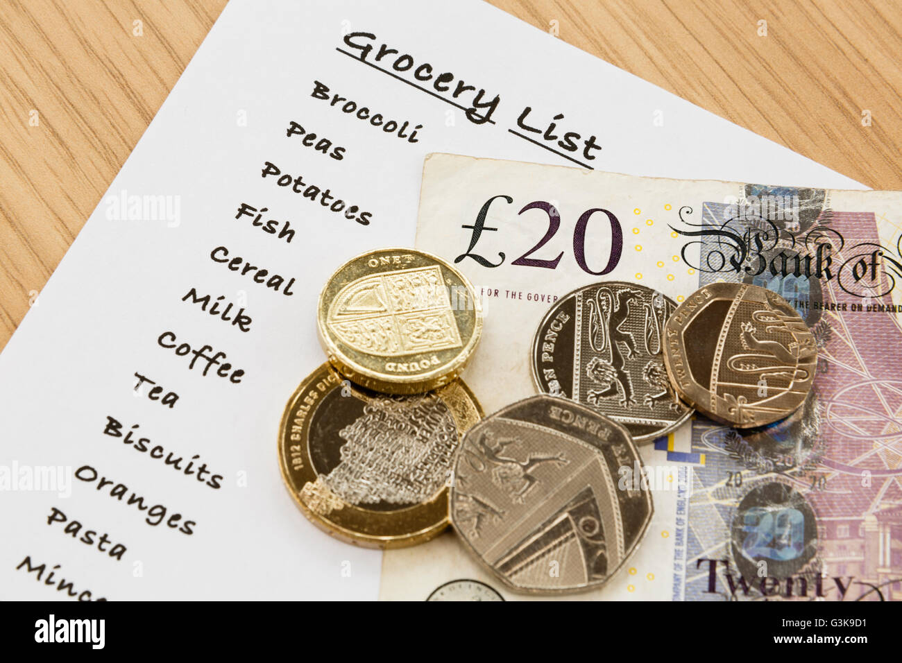 Shopping list for groceries with sterling money cash from above. England, UK, Britain Stock Photo