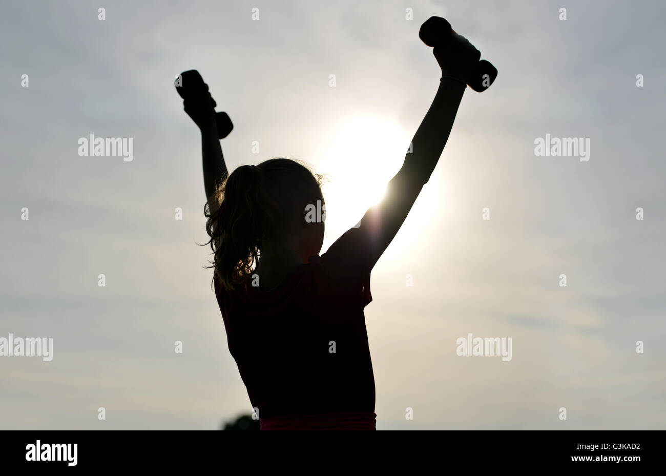 Silhouette of girl exercising outside - Stock Image