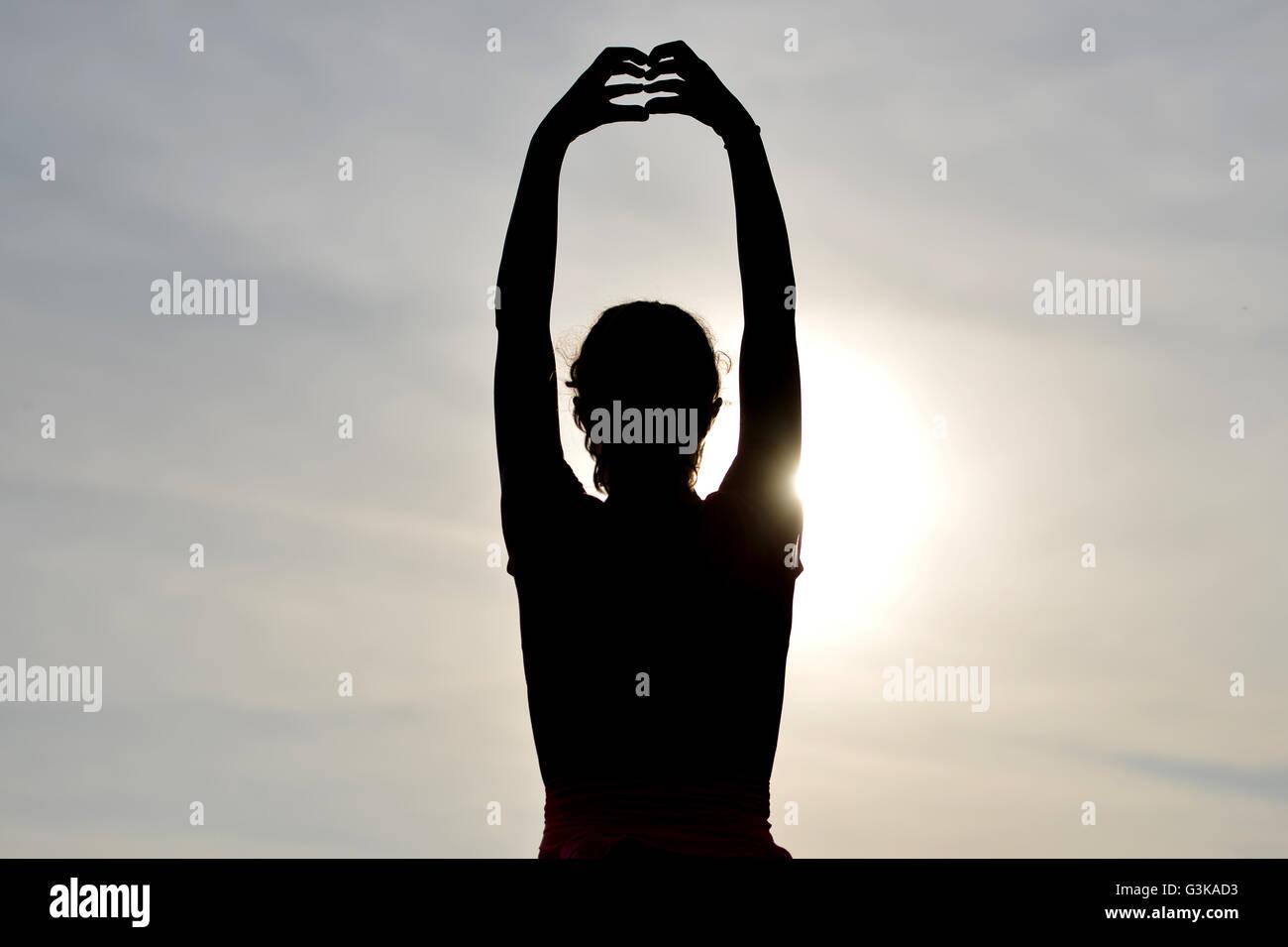 Silhouette of girl exercising outside - Stock Image