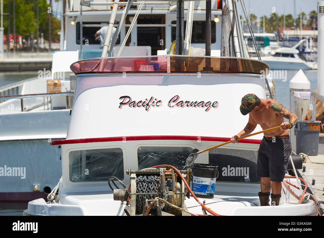 Fisherman Scrubs The Pacific Carnage In Rainbow Harbor, Long Beach. - Stock Image