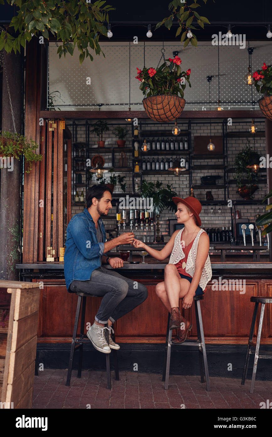 Full length shot of young couple sitting at cafe counter. Young man and woman sharing cigarette at coffee shop. - Stock Image
