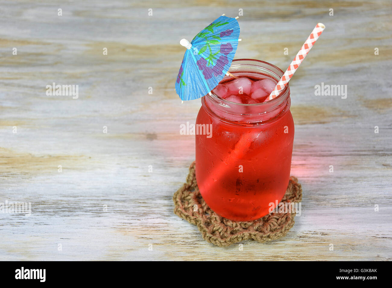 Fruit Punch Drink With Paper Umbrella And Gingham Straw In Glass Mason Jar On Weathered Wood